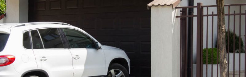 biały samochód wjeżdżający do garażu