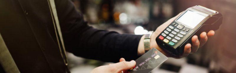mężczyzna trzymający terminal płatniczy i kartę