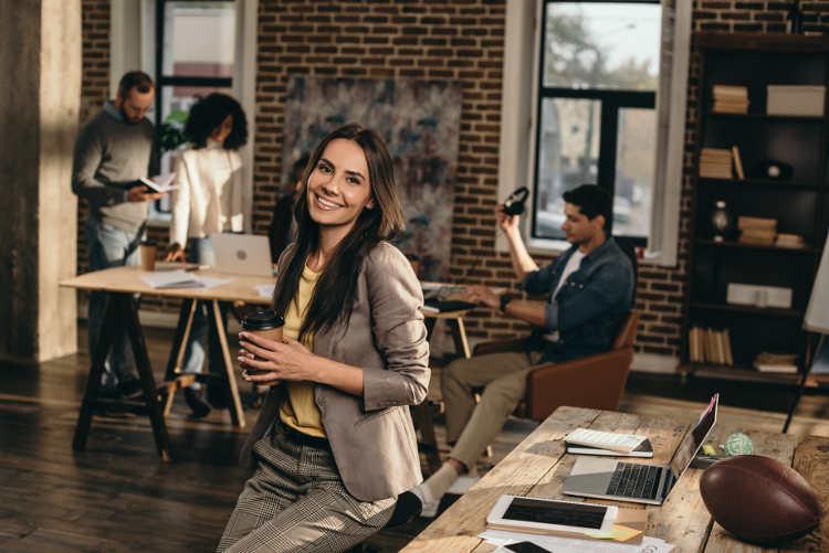 kobieta opierająca się o biurko a w tle koledzy z pracy