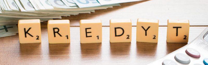 banknoty i kalkulator na blacie oraz kostki z napisem kredyt
