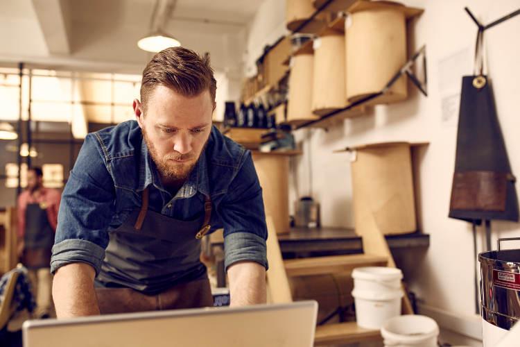 mężczyzna, właściciel kawiarni przy komputerze