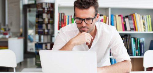 mężczyzna w okularach siedzący przed laptopem