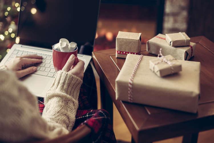 osoba przy komputerze z kubkiem w dłoni, a obok stół pełen prezentów