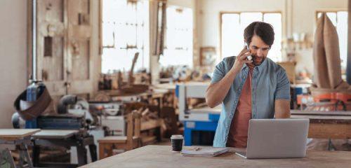 przedsiębiorca w zakładzie stojący przy laptopie