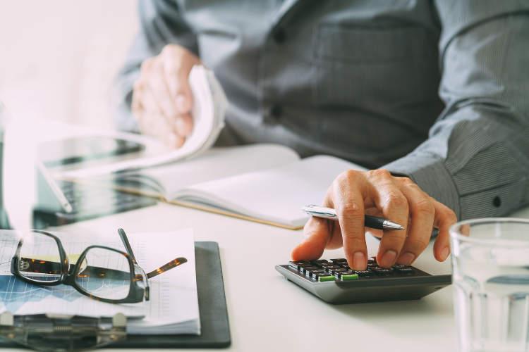 mężczyzna przy biurku prowadzący obliczenia na kalkulatorze