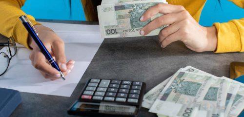 kobieta siedząca przy biurku z plikiem banknotów w dłoni robiąca obliczenia na kartce papieru