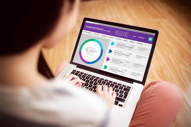 kobieta z laptopem na kolanach korzystająca z bankowości elektronicznej