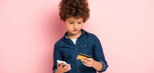 chłopiec z kartą kredytową i telefonem komórkowym na różowym tle