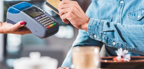 mężczyzna w niebieskiej koszuli przykładający kartę kredytową do terminala