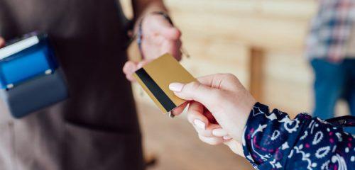kobieca dłoń przekazująca kartę kredytową mężczyźnie z terminalem płatniczym