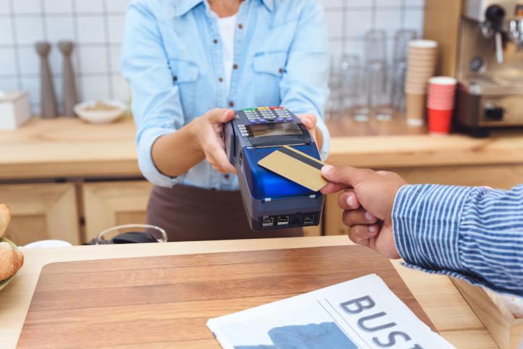 mężczyzna w kawiarni przykładający kartę kredytową do terminala