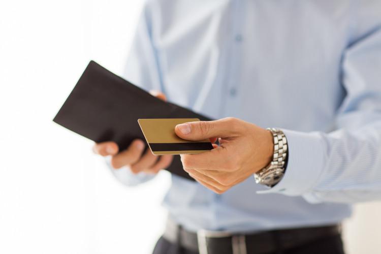 mężczyzna w błękitnej koszuli trzymający w jednej dłoni portfel a w drugiej kartę kredytową