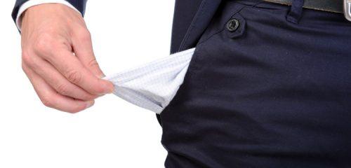 mężczyzna w granatowym garniturze wyciągający na zewnątrz pustą kieszeń spodni