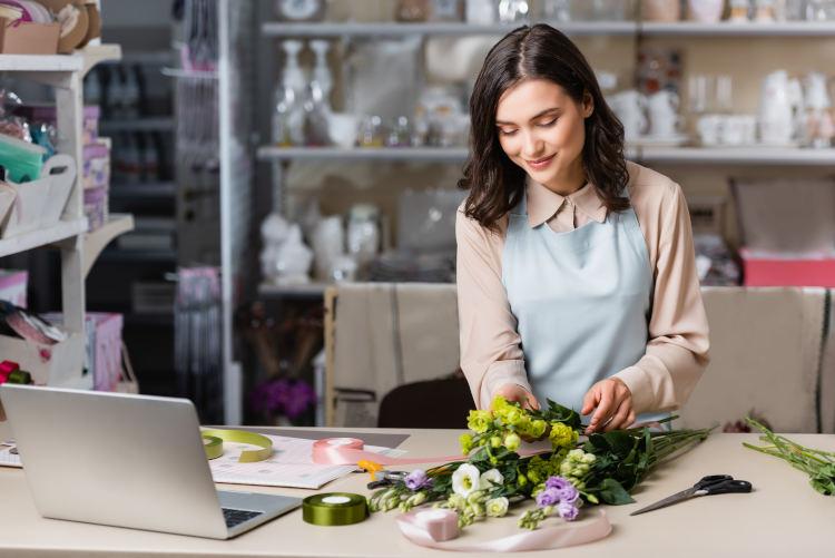 kwiaciarka w błękitnym fartuchu układająca bukiet kwiatów na blacie, na którym leży również otwarty laptop