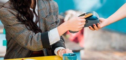 kobieta w kraciastej marynarce płaci kartą kredytową za kawę
