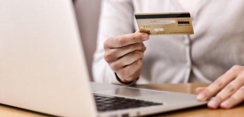 kobieca dłoń trzymająca złotą kartę kredytową nad otwartym laptopem
