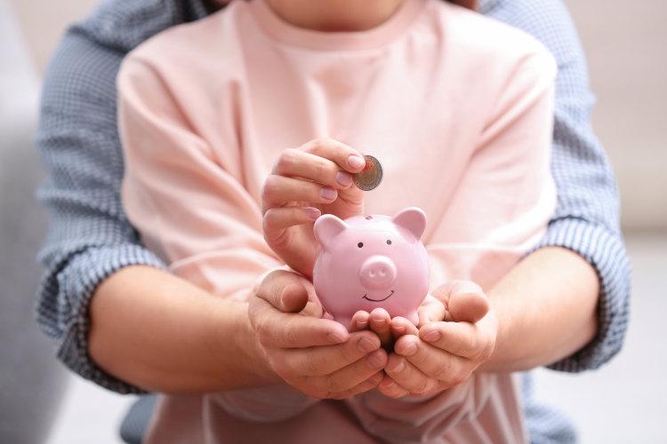dziecko i rodzic trzymające świnkę skarbonkę