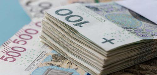 paczka banknotów stuzłotowych leżąca na banknotach 500 złotowych