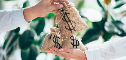 dłoń przekazująca na inne dłonie materiałowe worki z symbolem pieniędzy