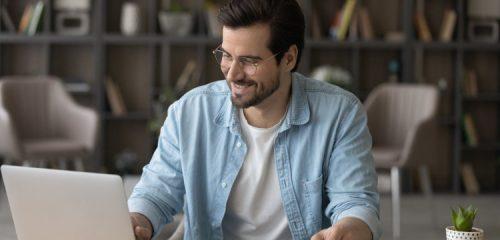 zadowolony mężczyzna w niebieskiej koszuli siedzący przed laptopem