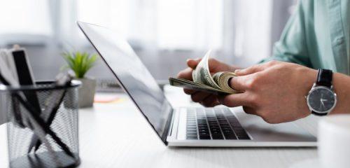 osoba przy otwartym laptopie przeliczająca plik banknotów