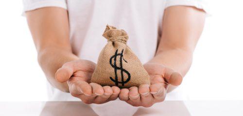 worek z pieniędzmi położony na dłoniach mężczyzny w białej koszulce