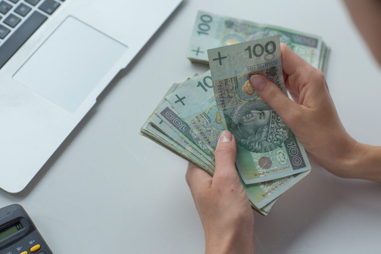 kobiece dłonie trzymające nad biurkiem plik stuzłotowych banknotów