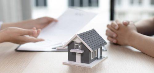 makieta szarego domku na blacie biurka w tle osoba podpisująca umowę