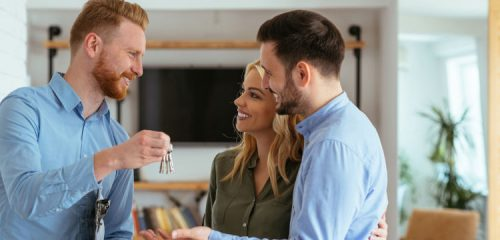 Pośrednik w sprzedaży nieruchomości trzymający klucz do mieszkania i szczęśliwa para
