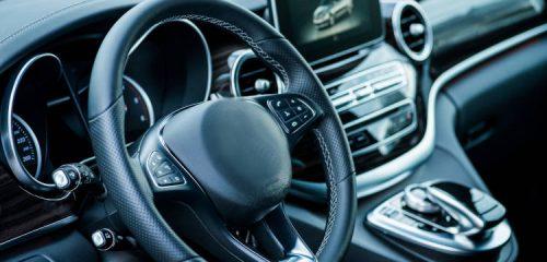 deska rozdzielacza luksusowego samochodu. Kierownica na pierwszym planie kierownica. W tle monitor.