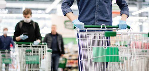 osoby w supermarkecie pchające puste wózki