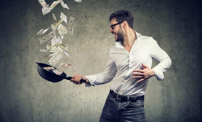 Gość podrzuca pieniądze na patelni.