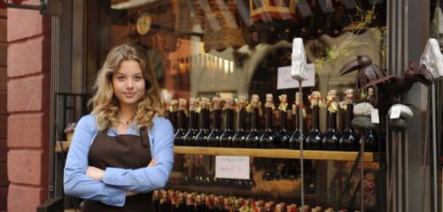kobieta w brązowym fartuchu stojąca przed witryną