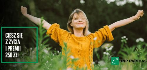 kobieta w pomarańczowym swetrze stojąca z uniesionymi rękami wśród roślinności